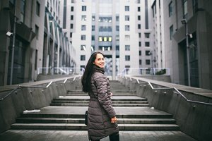 portrait of a woman on a business theme. Young Caucasian brunette girl in long jacket, coat with black leather bag stands on business center background, office building with glass facade