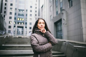 portrait of a woman on a business theme. Young caucasian brunette with long hair girl in long jacket, coat stands on business center background, office building with glass facade. Overcast in winter
