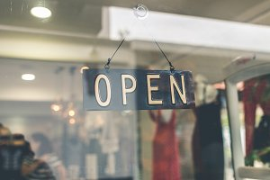 Open sign broad through the glass of store window. Asia.