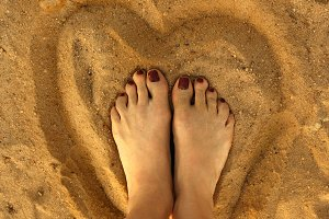 Two femile pedicured feet, on the sand inside sand heart