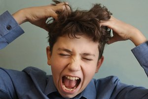 preteen handsome boy scratch his head itch because of lice invasion