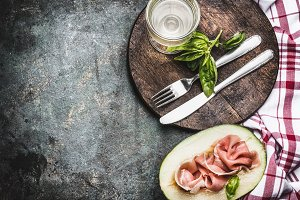 Melon with ham , wine and cutlery