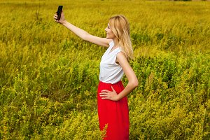 Girl in the field with phone.