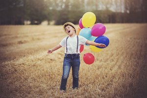 happy boy with balloons in the field