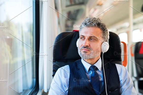 Mature Businessman With Headphones Travelling By Train