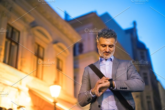 Mature businessman with a smartwatch in a city.