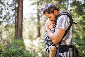 Young father with little boy in forest, summer day.
