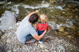 Young father with little boy at the river, summer day.
