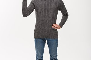 Holiday Concept - Young beard man in sweater enjoy playing and pointing finger upward.