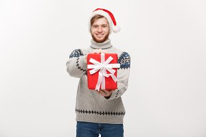 Holiday Concept - young handsome man giving red present to camera.