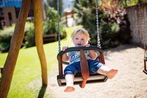 Little boy on the swing at the playground.
