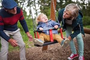 Senior couple with little boy at the playground.
