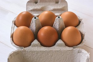 Fresh brown eggs in a carton