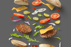 Burger ingredients against dark grey background