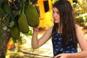 teenager girl with whole jackfruit on the tree