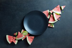 black plate and slices of fresh watermelon