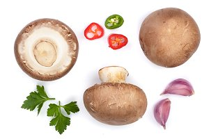 Fresh champignon mushrooms with parsley, and red hot chili peppers isolated on white background. Top view