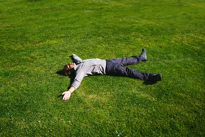 Happy man lying on the grass