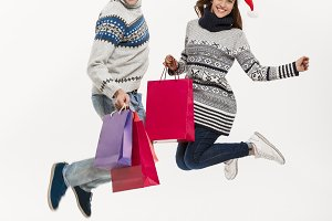 Christmas Concept - Full length Young attractive couple holding shopping bags and jumping isolated on white grey background.