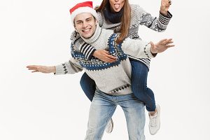 Christmas Concept - Young happy couple in sweaters enjoying piggyback ride isolated on white grey background