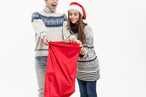 Christmas Concept - Full length Young attractive couple holding santa bag isolated on white grey background.