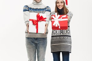 Christmas Concept - Young adorable couple holding presents isolated on white grey background.