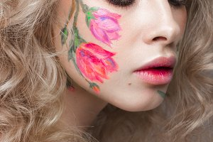 Beautiful blond girl with curls and a floral pattern on the face. Beauty flowers.