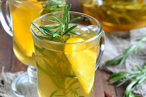 Healthy orange rosemary tea on wooden background