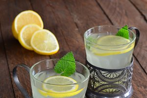 Hot ginger lemon drink on wooden background