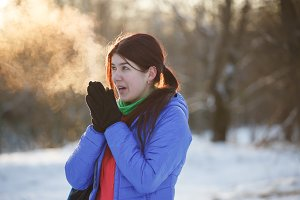 Photo of brunette warming hands in winter at woods