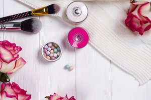 Women cosmetics and fashion items on white wooden background