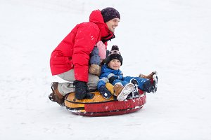 Picture of father, son, daughters riding tubing in winter park