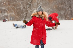 Photo of woman in red jacket during snowfall
