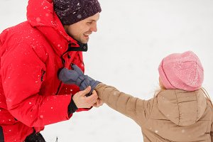 Picture of father dressing his daughter in winter park at winter