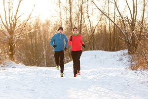 Image of running two athletes in winter park