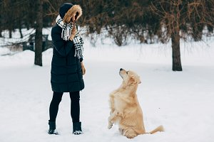 Image of woman with retriever walking in winter park