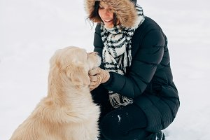 Photo labrador giving paw to girl in black jacket in winter afternoon
