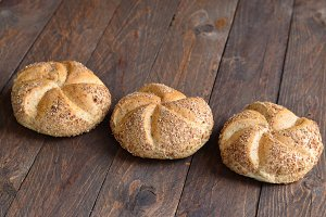 Multigrain Kaiser rolls on wooden background