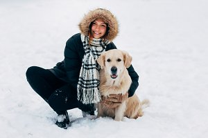 Photo of smiling woman with dog in winter park
