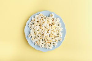 popcorn in a blue plate on a yellow