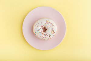 white donut, pink plate on a yellow