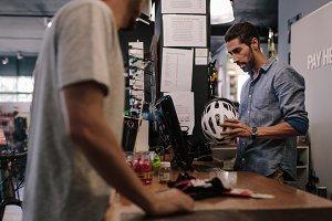Shop owner selling helmet