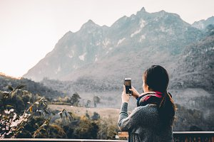 Young Woman taking photo with her phone of beautiful mountain view