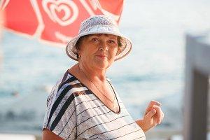 Beautiful elderly woman in a hat on a beach