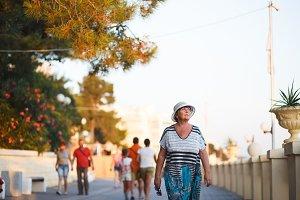 Elegant mature woman walking on promenade during summer sunset in park