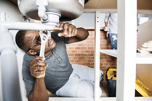Plumber man fixing kitchen sink