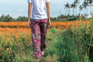 Pretty woman walking in marigold field in the valley. Tropical island of Bali, Indonesia.