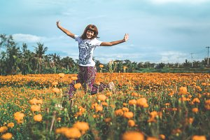 Pretty woman jumping in marigold field in the valley. Tropical island of Bali, Indonesia.