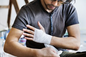 Man bandaging injured hand