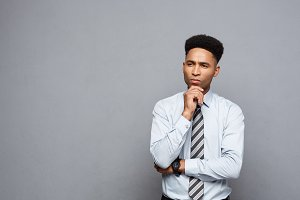 Business Concept - Confident professional african american businessman in thinking posture over grey background